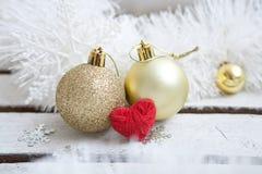 Stäng sig upp av flera guld- glass struntsaker för jul med röd hjärta Royaltyfria Bilder