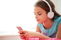Stäng sig upp av flicka med smartphonen och hörlurar royaltyfri foto