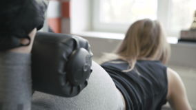 Stäng sig upp av flickan som utarbetar med simulatorn för bakdelar i idrottshallen 4K arkivfilmer