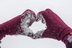 Stäng sig upp av flickan som visar ett hjärtasymbol vid händer i vintern arkivfoton