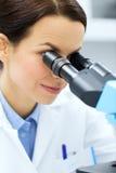 Stäng sig upp av forskaren som ser till mikroskopet i labb Arkivbild