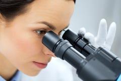Stäng sig upp av forskaren som ser till mikroskopet i labb Royaltyfri Bild