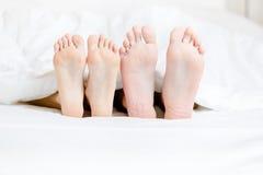 Stäng sig upp av fot av paren som ligger i sovrum royaltyfri fotografi