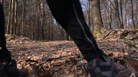Stäng sig upp av fot för en idrottsman nen som kör på den mest forrest vägen Långsam mo arkivfilmer