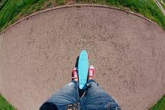 Stäng sig upp av fot på blått plast- encentmyntskridskobräde med pinlhjul royaltyfria foton