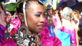 Stäng sig upp av framsidor av folk och kulturella dansare i kokosnötdräktdans längs gatorna för att fira skyddshelgonet stock video