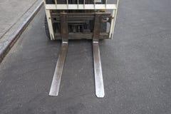 Stäng sig upp av gaffeltruckblad på en stads- stadsgatablacktop arkivfoto