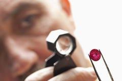 Stäng sig upp av gemstonen med juveleraren som ser till och med förstoringsglaset Royaltyfri Fotografi