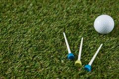 Stäng sig upp av golfboll med utslagsplatsen på fält Royaltyfri Bild