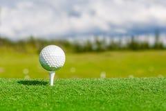 Stäng sig upp av golfboll och utslagsplats med med suddig bakgrund arkivbild