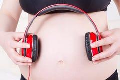 Stäng sig upp av gravid kvinna med hörlurar på buklisteninen royaltyfria foton