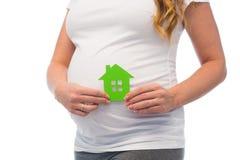 Stäng sig upp av gravid kvinna med symbolen för det gröna huset Arkivfoton