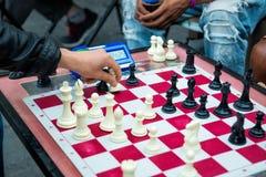Stäng sig upp av händer av folk som spelar snabbt schack på gatan med tidmätaren Royaltyfri Foto