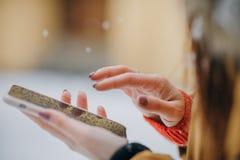 Stäng sig upp av händer genom att använda den moderna smarta telefonen i vinterstaden arkivfoto