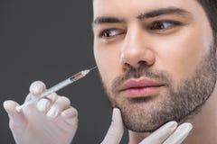stäng sig upp av händer i medicinska handskar som gör skönhetinjektionen för man, royaltyfri foto
