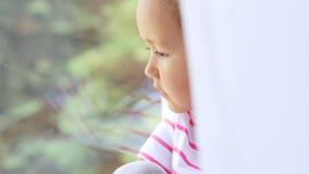 Stäng sig upp av händer på knä av gulligt liten flickasammanträde på fönsterbräda av fönstret arkivfilmer