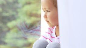 Stäng sig upp av händer på knä av gulligt liten flickasammanträde på fönsterbräda av fönstret stock video