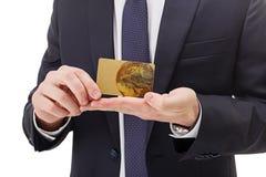 Stäng sig upp av händer som rymmer det guld- kortet på vit bakgrund fotografering för bildbyråer