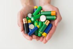 Stäng sig upp av händer som rymmer högen för alkaliska batterier Royaltyfri Fotografi