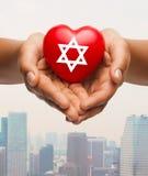 Stäng sig upp av händer som rymmer hjärta med den judiska stjärnan Royaltyfria Bilder