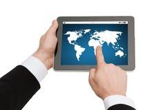Stäng sig upp av händer som rymmer minnestavlaPC med världskartan Fotografering för Bildbyråer