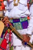 Stäng sig upp av händer som rymmer svärdet under konkurrens för herr Desert, Ja Royaltyfria Bilder