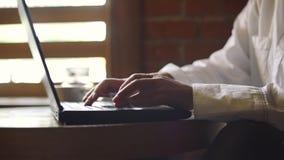 Stäng sig upp av händer som skriver på en bärbar dator i ett kafé stock video