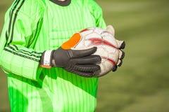 Stäng sig upp av händerna av målvakten som rymmer en soccerball Arkivfoto
