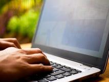 Stäng sig upp av händerna av en tele arbetare som skriver på ett bärbar datortangentbord med en suddig bakgrund royaltyfri bild