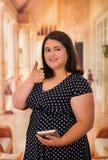 Stäng sig upp av härlig fet kvinna i en härlig klänning genom att använda hennes minnestavla med dunsar upp, i en suddig bakgrund royaltyfri foto