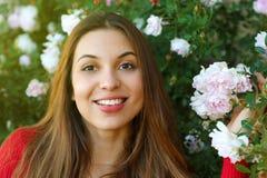 Stäng sig upp av härlig naturlig kvinna i trädgården mellan blommor royaltyfria bilder