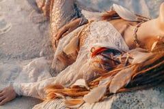 Stäng sig upp av härlig ung kvinna i den eleganta klänningen som ligger på sand på stranden på solnedgångtid arkivbild