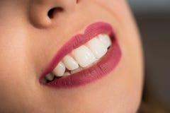 Stäng sig upp av härlig ung le kvinna med perfekta tänder i tand- kontor royaltyfri bild