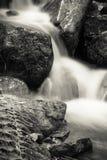 Stäng sig upp av härliga silkeslena mjuka flodvattenfall som flödar i höstlandskapskog med döda sidor i svartvitt, Frankrike Fotografering för Bildbyråer