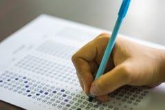 Stäng sig upp av högstadiet eller universitetsstudenten som rymmer en pennhandstil på papper för svarsarket i undersökningsrum Hö Arkivfoto