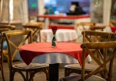 Stäng sig upp av höjdpunkten av en spansk restaurangtabell med röda rutiga bordduk- och trästolar arkivbilder