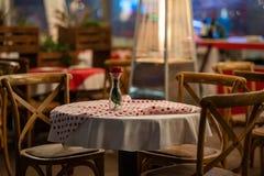 Stäng sig upp av höjdpunkten av en spansk restaurangtabell med röda rutiga bordduk- och trästolar arkivbild