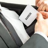 Stäng sig upp av handen av en bankir som visar ett kort läsande Banke Royaltyfri Fotografi