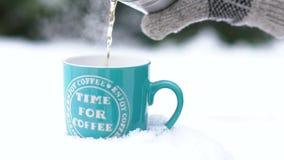 Stäng sig upp av handen i handsken som häller varmt te från termoset in i koppen på snö långsamt arkivfilmer