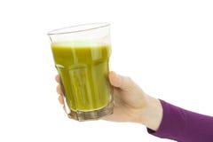 Stäng sig upp av handen som rymmer ett exponeringsglas av den gröna grönsaksmoothien Royaltyfria Foton