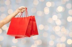 Stäng sig upp av handen som rymmer röda shoppingpåsar Royaltyfri Foto