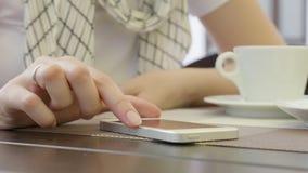 Stäng sig upp av handkvinnan som använder hennes mobiltelefon i restaurangen, kafé arkivfilmer