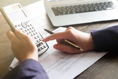 Stäng sig upp av handmannen som gör finanser och, beräkna på skrivbordet om hemmastatt kontor för kostnad Besparingar, finanser o arkivfoton