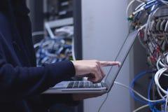 Stäng sig upp av handteknikeren som arbetar på bärbara datorn i datorhall Annons arkivfoto