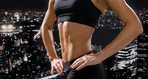 Stäng sig upp av idrotts- kvinnlig abs i sportswear Arkivfoton