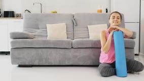 Stäng sig upp av iklätt blått jogga för ung härlig kvinna eller en kondition som är matta, når du har arbetat hemma i vardagsrumm lager videofilmer