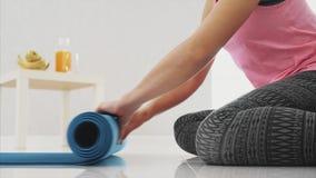 Stäng sig upp av iklätt blått jogga för ung härlig kvinna eller en kondition som är matta, når du har arbetat hemma i vardagsrumm stock video