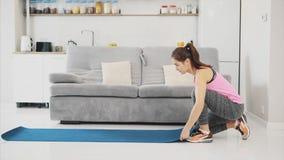 Stäng sig upp av iklätt blått jogga för ung härlig kvinna eller en kondition som är matta, når du har arbetat hemma i vardagsrumm arkivfilmer