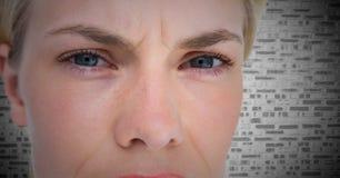 Stäng sig upp av ilskna ögon för kvinna` s mot den vita tegelstenväggen Fotografering för Bildbyråer
