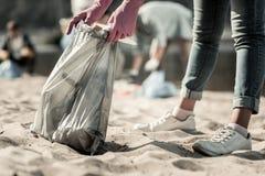 Stäng sig upp av jeans och gymnastikskor för ung student som bärande upp gör ren avfall på stranden arkivfoton